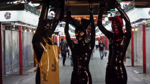 vídeos de stock, filmes e b-roll de figures dressed in latex suits pose in front of the camera as onlookers pass by to observe them. the characters dressed in full latex costumes pose under a japanese lantern on a busy street in tokyo. - látex borracha