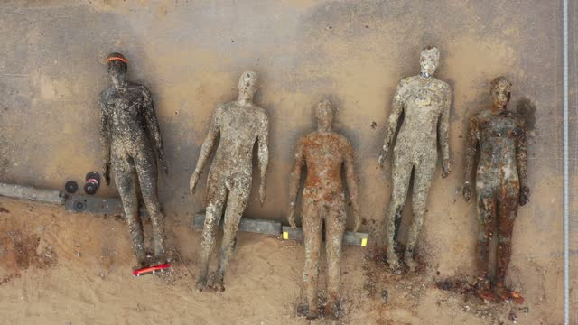 figures from artist sir antony gormley's installation 'another place' on crosby beach, lay on the ground as they are affixed with new mountings on... - the human body stock videos & royalty-free footage