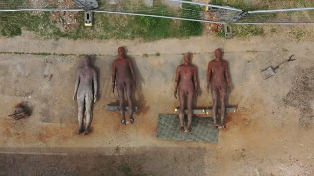 figures from artist sir antony gormley's installation 'another place' on crosby beach, lay on the ground as they are affixed with new mountings on... - sculpture stock videos & royalty-free footage