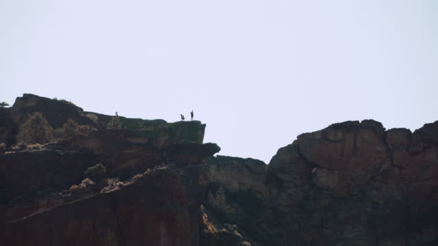 figures on clifftop, rocky desert landscape - smith rock, oregon, panning shot - oregon us state stock videos & royalty-free footage