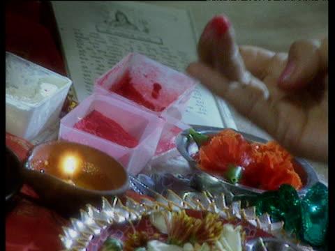 figurine of goddess lakshmi in being decorated in diwali ritual with red dot (bindi) - bindi stock videos and b-roll footage
