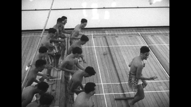 vidéos et rushes de vs fijian men in ethnic clothing perform dance on ship's deck / launch approaches ship that has british naval flag flying / tilt down queen elizabeth... - marine
