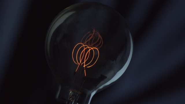 filaments heat to provide light from an incandescent bulb. - incandescent bulb stock videos and b-roll footage
