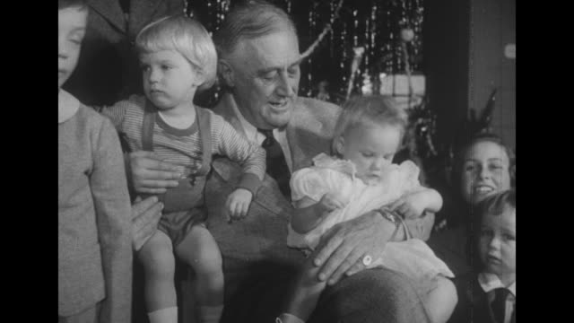 vídeos y material grabado en eventos de stock de president roosevelt seated in front of christmas tree surrounded by daughter anna sons elliot fdr jr daughtersinlaw ethel du pont anne lindsay clark... - franklin roosevelt