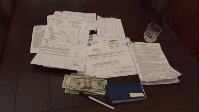 files, documents and cash litter a desk. - investment stock videos & royalty-free footage
