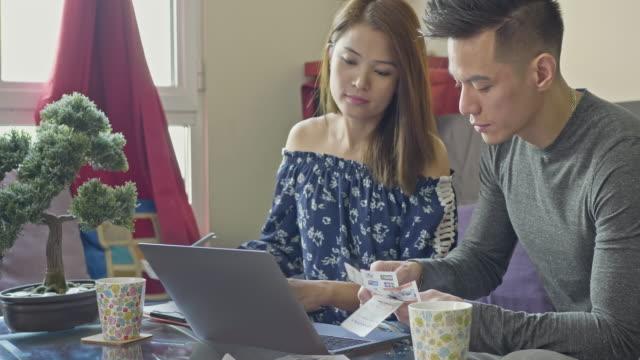 vídeos de stock, filmes e b-roll de casal filipino calcular as contas em casa - filipino