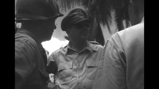 vídeos y material grabado en eventos de stock de vs filipino huts aflame amid banana and palm trees vs large troop carrier and soldiers walking through mired road / gen douglas macarthur exits jeep... - douglas macarthur