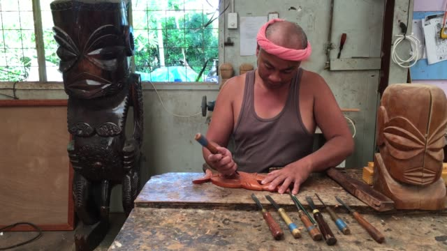 Filipino man wood curving in a workshop