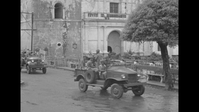 vs filipino soldiers marching past old spanish church / closer view soldiers / jeeps with soldiers passing by church / destroyers in manila bay /... - ジープ点の映像素材/bロール