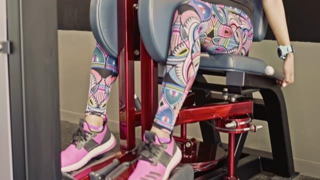 filipino woman exercising on leg press machine at gym - leg press stock videos & royalty-free footage