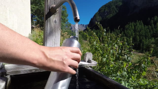 fill a gourd in a fountain in a mountain village - bottle stock videos and b-roll footage