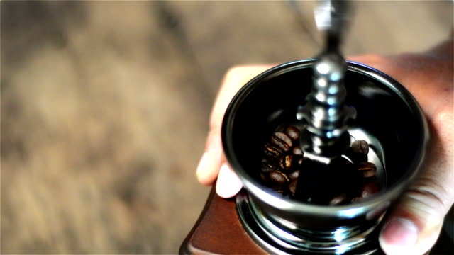 filled coffee beans into coffee grinder and grinds coffee bean. - grinding stock videos and b-roll footage