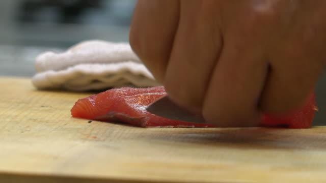 fillet raw fish with knife (sashimi) - bordsduk bildbanksvideor och videomaterial från bakom kulisserna