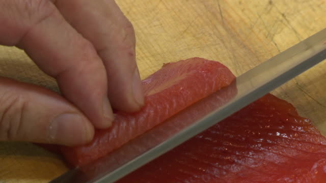 Fillet raw fish with knife (Sashimi)