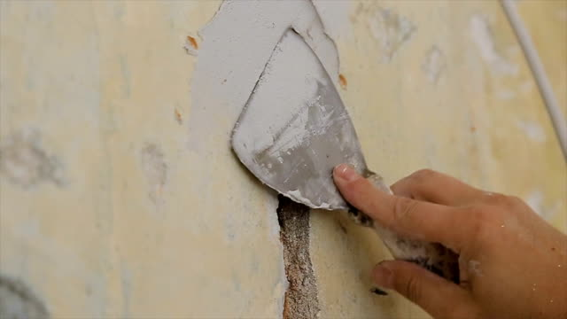 filling a hole in the wall with construction material,close up - aggiustare video stock e b–roll
