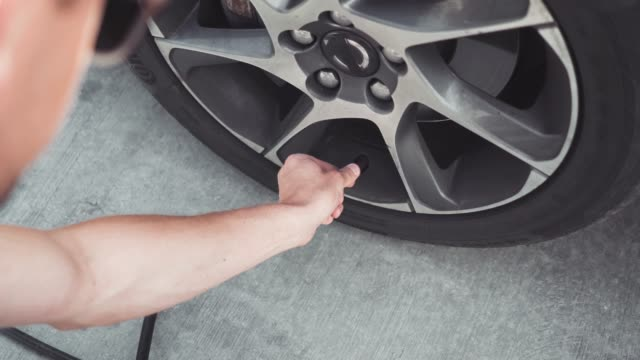 filling air into a car tire - examining stock videos and b-roll footage