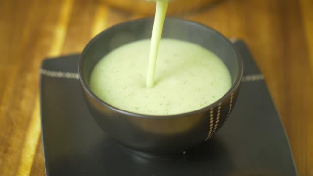 vidéos et rushes de soupe de chou-fleur de remplissage dans un bol en grès noir - bol à soupe