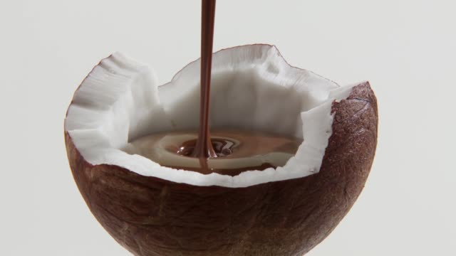 filling half a coconut with chocolate sauce - ココナッツ点の映像素材/bロール