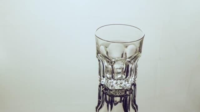 vídeos de stock e filmes b-roll de filling ice cube into empty glass. - copo vazio