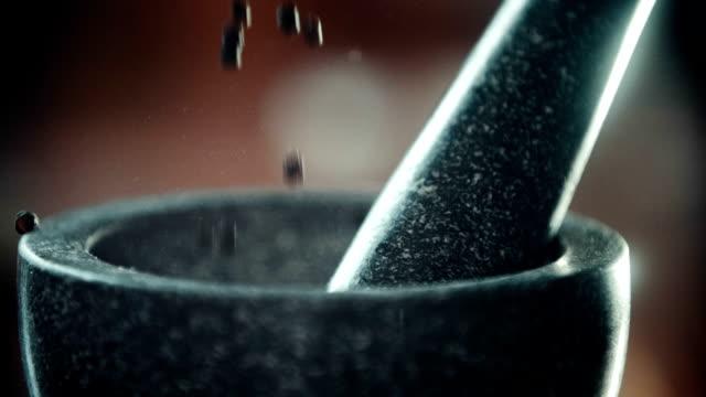 vídeos y material grabado en eventos de stock de llenado peppercorns en un mortero con mazo - picar preparar comida
