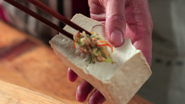 filling stir-fried veggies into the slit of tofu - reportage stock videos & royalty-free footage