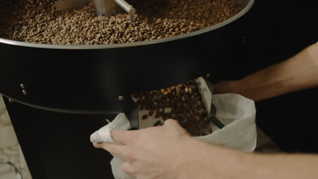 filling the bag with coffee slow motion 4k - sacca video stock e b–roll
