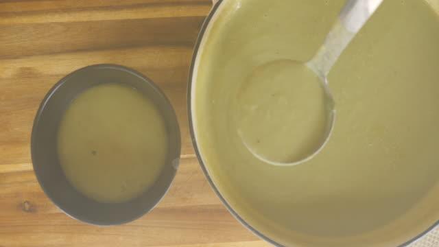 vidéos et rushes de remplir la soupe de pommes de terre de poireaux dans un bol - bol à soupe