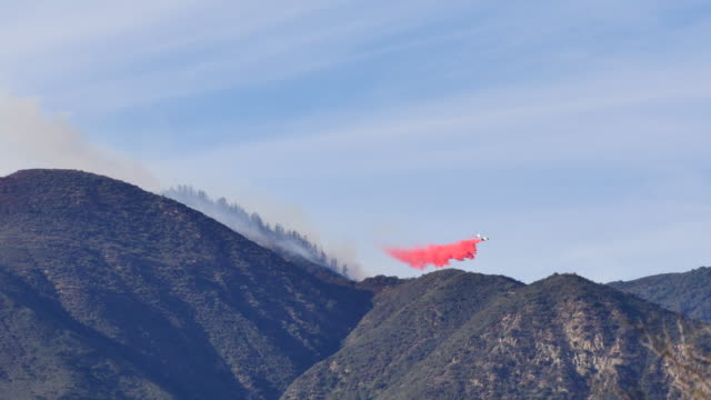 a tanker aircraft drops red fire retardant onto the thomas fire near fillmore california december 9 2017 firefighters from across california and the... - 2017 stock videos & royalty-free footage
