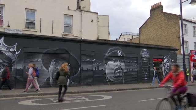 Film about gentrification in Brixton Film about gentrification in Brixton ENGLAND London Brixton EXT People along street past murals on wall Sign...