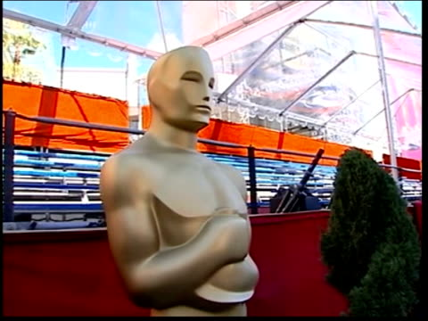 Academy Awards USA Los Angeles Kodak Theatre EXT Theatre being prepared including giant 'Oscar' statues Assistants carrying statuette trophies along...