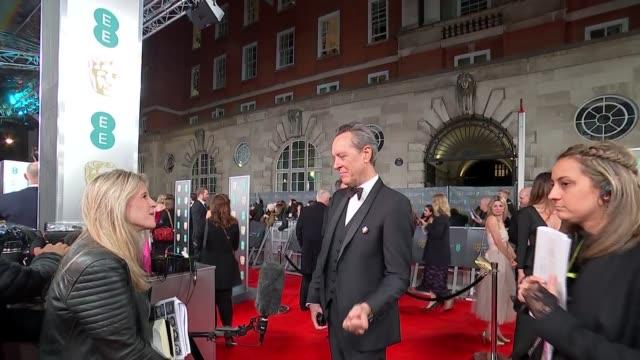 vídeos de stock e filmes b-roll de film awards 2020: red carpet arrival interviews; england: london: royal albert hall: bafta film awards 2020: ext / night richard e grant talking to... - richard e. grant