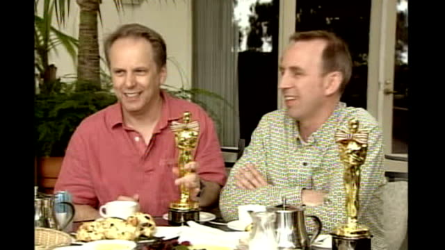 british animators nominated for oscar; 2006 usa: nick park seated at table with oscar statues - animator stock videos & royalty-free footage