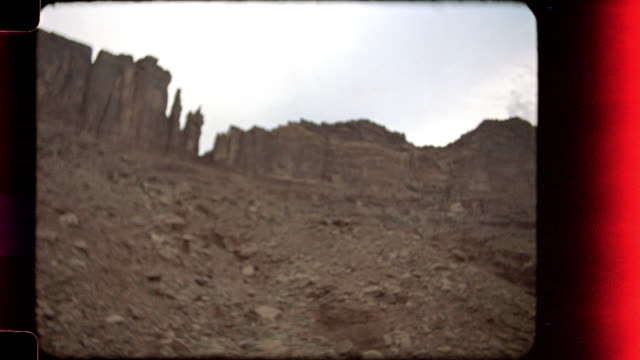 film camera pans across sandstone rock formations and over colorado river in vintage nature footage. - remote location video stock e b–roll