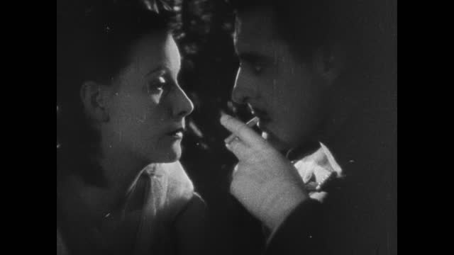 Film can 'Flesh and the Devil' onto Robin Hood can CLIP Greta Garbo John Gilbert in match light Garbo blowing match out DIALOG CARD 'You know when...