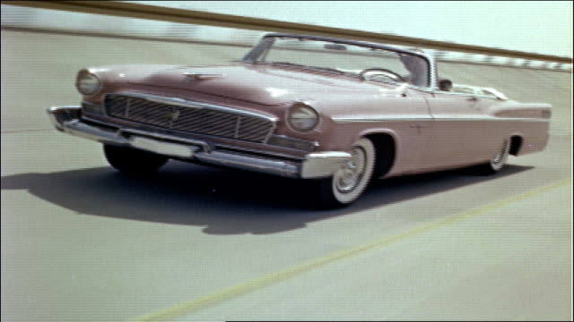 Film clapboard held to camera VS pink 1956 New Yorker convertible driving on highway Convertible with hood raised parked next to two other cars