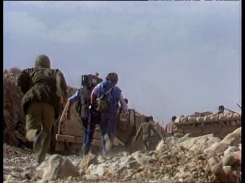 film crew and soldiers run over rubble throw themselves on ground for protection against iraqi fire iran iraq war; 1984 - イラク点の映像素材/bロール