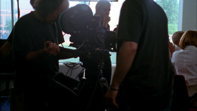 A film crew captures an office scene by moving around a conference table on a dolly.