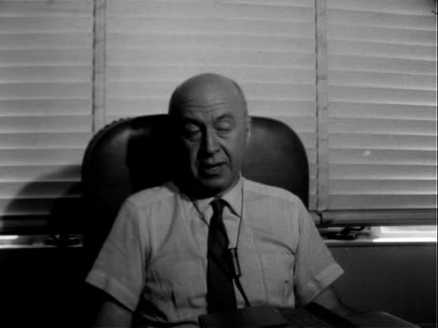 vídeos de stock e filmes b-roll de film director otto preminger sitting in leather chair at desk reading book / otto preminger lowering book responding to questions about directing the... - dirigir