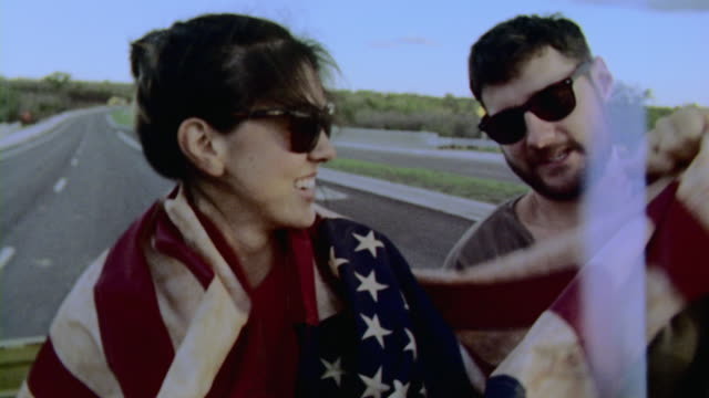 Film footage of friends on road trip draped in American flag in backseat of classic Ford Bronco