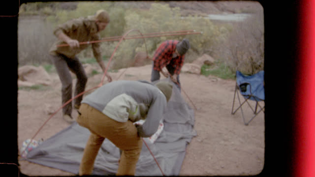Film footage of three young men building a tent at Utah camp site.