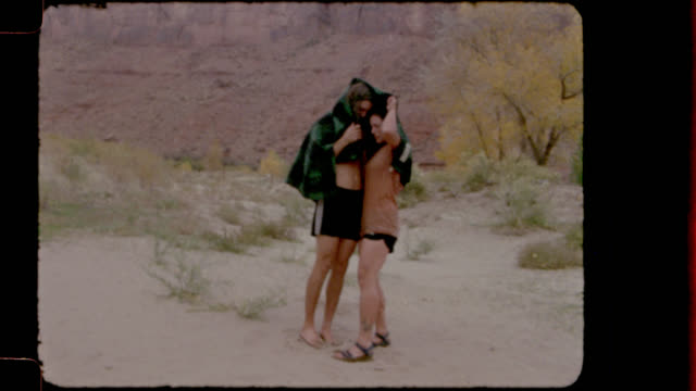 Film footage of young couple on camping trip hiding under towel and jumping to keep warm after swimming in the river.