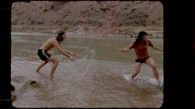 vídeos de stock e filmes b-roll de film footage of young couple on camping trip wading into river and splashing each other with cold water. - memorial