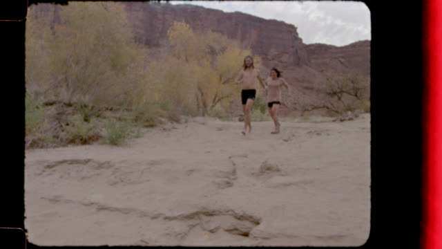 vídeos de stock e filmes b-roll de film footage of young man and woman on camping trip running down the rocks to jump in the colorado river. - território selvagem