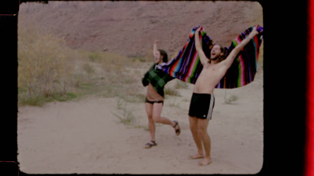 Film footage of young man and woman wrapped in towels cheering after swimming in the river.