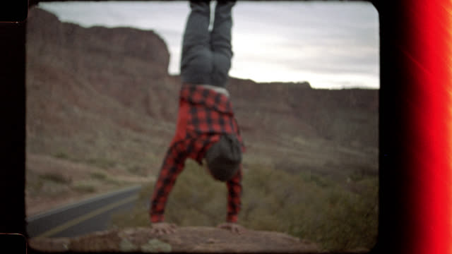 Film footage of young man doing handstand on boulder and throwing hands in the air on Moab climbing trip.