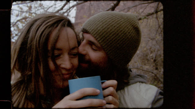 Film footage of young man on camping trip giving his girlfriend a kiss on the cheek.