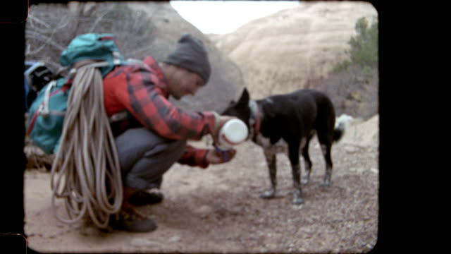 Film footage of young man pouring water into his hand for dog to drink and friends lounging on the rocks on Moab hiking trip.