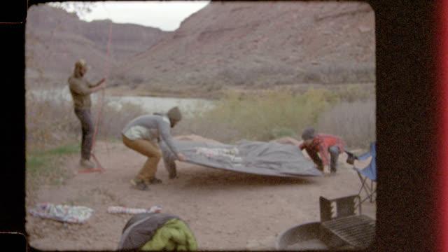 vídeos y material grabado en eventos de stock de film footage of young men spreading groundsheet to set up tent at utah camp site. - borde