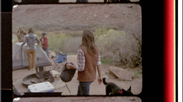 Film footage with multiple splices of friends setting up tent at camp site and dog wandering around campground.