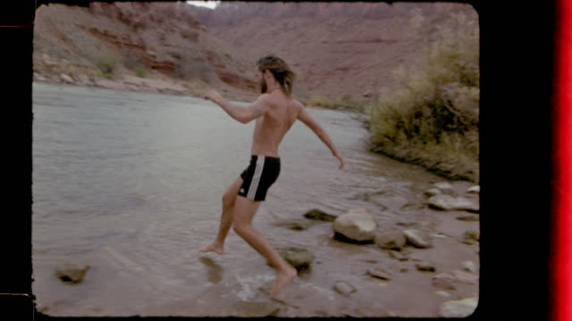Film footage with multiple splices of young man and woman playing and splashing in the Colorado River on Utah camping trip.
